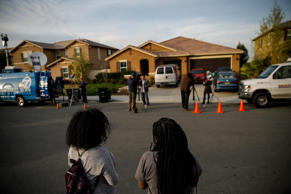 Neighbors stand outside the day after a Perris husband and wife are in custody on suspicion of torture and child abuse at a home on 100 Block of Muir Woods Road, in Perris, Calif., on Jan. 15, 2018.