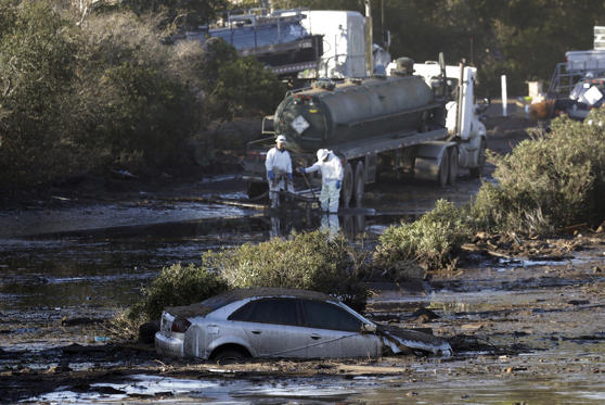 Slide 1 of 71: Crews pump mud on Highway 101 after a mudslide Saturday, Jan. 13, 2018, in Montecito, Calif.  Most of the people of Montecito, a town usually known for its serenity and luxury, were under orders to stay out of town as gas and power were expected to be shut off Saturday for repairs.