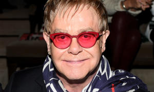 Elton John wearing glasses and smiling at the camera: Hello! Magazine