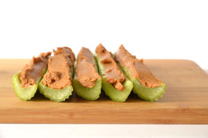 Healthy snack - Celery stalks with peanut butter Laying on wooden cutting board