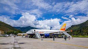 Paro: People arriving at Paro airport, Bhutan with druk air, the 'dragon airline', the only airline that is aloud to land in Bhutan. In the background are the mountains.