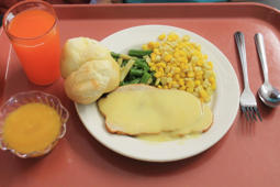A pink cafeteria tray with a plate of food, drink, dessert and silverware on it.