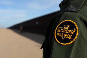 A U.S. border patrol agent walks along the border fence between Mexico and the United States near Calexico, California, U.S. February 8, 2017. Picture taken February 8, 2017.
