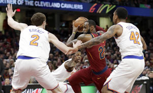 Cleveland Cavaliers' LeBron James, center, drives past New York Knicks' Luke Kornet, left, from Switzerland, and Lance Thomas in the first half of an NBA basketball game, Wednesday, April 11, 2018, in Cleveland. (AP Photo/Tony Dejak)