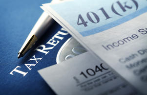 A 401k statement rests on top of a U.S. Federal 1040 income tax return and is photographed using a very shallow depth of field. This image conveys the tax implications of saving for and taking distributions from retirement accounts.