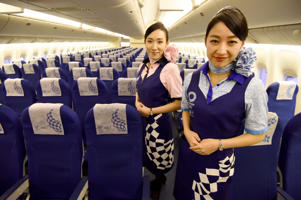 Flight attendants for Japanese airline All Nippon Airways (ANA) pose to display aprons and headrest covers printed with emblems of the 2020 Tokyo Olympic Games and Paralympic Games, inside the company's 'Hello 2020 Jet' inside an ANA hanger at Haneda Airport in Tokyo on January 28, 2018. The plane, which has an Olympic livery, will be used for domestic flights from January 29 until the Olympic Games and Paralympic Games in 2020. / AFP PHOTO / Toru YAMANAKA (Photo credit should read TORU YAMANAKA/AFP/Getty Images)