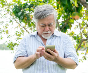 Senior man trying to use a mobile device