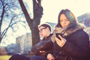 Woman sitting in the park with a man and using smart phone