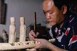 An ivory carver at working in a factory