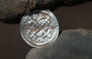 An archaeologist holds Denmark's first independent type of coin after its excavation in Schaprode, northern Germany on April 13, 2018.
