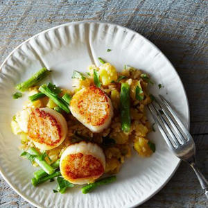a bowl of food on a plate: Dale Talde's Grilled Scallops with XO-Pineapple Fried Rice