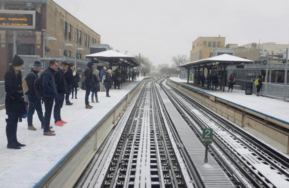Slide 1 of 6: Commuters wait for trains as snow falls Monday, April 16, 2018, in Chicago. (AP Photo/Kiichiro Sato)