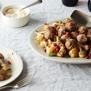 a bowl of food on a table: Sheet Pan Lamb Meatballs with Cauliflower and Tahini-Yogurt Sauce