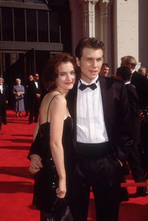 American actors Christian Slater and Winona Ryder pose while holding hands on the red carpet, as they attend the Academy Awards at the Shrine Auditorium, Los Angeles, California. That year the two starred in the film, 'Heathers.'