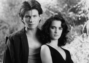 Christian Slater and Winona Ryder standing together in a scene from the film 'Heathers', 1988.