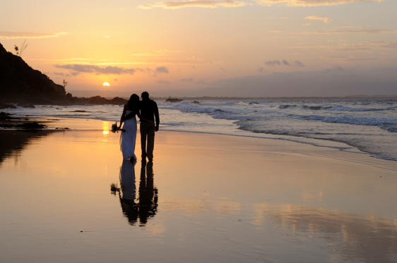 Slide 1 of 15: A newly married couple walking away together on the beach