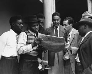 Some of the 482 Jamaicans emigrating to the UK read a newspaper on board the ex-troopship Empire Windrush which arrived at Tilbury. UK. (Photo by © Hulton-Deutsch Collection/CORBIS/Corbis via Getty Images)