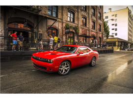 a red car parked on the side of a building: 2016 Dodge Challenger