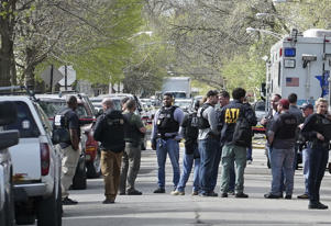 Police from various agencies investigate the scene where a Bureau of Alcohol, Tobacco, Firearms and Explosives agent was shot, Friday, May 4, 2018, in Chicago. Chicago police say they have deployed several hundred officers hunt for a man who shot and critically wounded the federal agent. (AP Photo/Teresa Crawford)