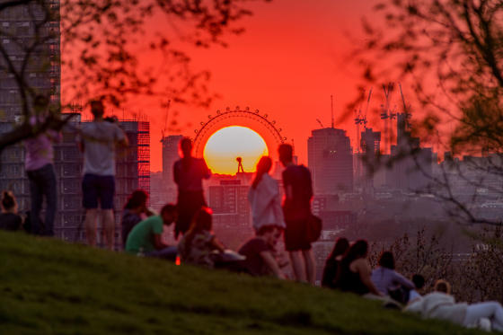 Slide 1 de 34: Londoners enjoying the magnificent sight of sun setting perfectly in the middle of London Eye as seen from Greenwich Park on the warmest day of the year