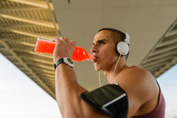 Handsome athlete drinking water after training.Photo of a young man drinking water .Water is a key to good workout.
