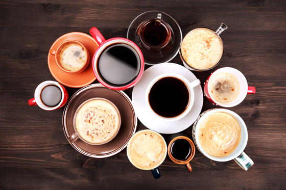 Slide 1 dari 21: Many different cups of coffee on dark wooden table, top view.