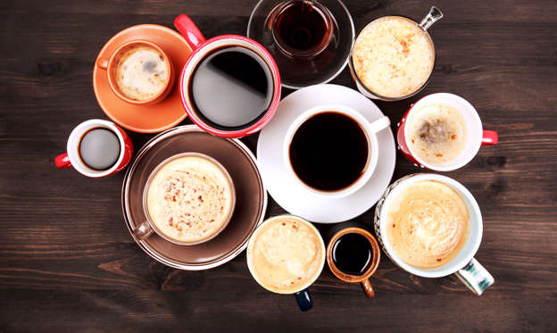 Lysbilde 1 av 21: Many different cups of coffee on dark wooden table, top view.
