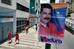 People walk by electoral posters of Venezuelan President and reelection candidate Nicolas Maduro in Caracas on April 22, 2018. - Maduro is seeking re-election on May 20 among voters grappling with hyper-inflation and shortages of food and medicine. (Photo by Luis ROBAYO / AFP)        (Photo credit should read LUIS ROBAYO/AFP/Getty Images)