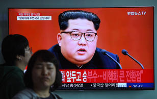 People walk past a television news screen showing file footage of North Korean leader Kim Jong Un at a railway station in Seoul on Saturday.
