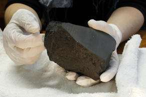 A French scientist holds a chondrite meteorite, the sort of rock the new study mimicked.