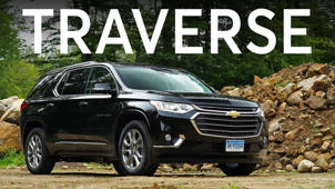 a car parked in front of a sign: 2018 Chevrolet Traverse Road Test