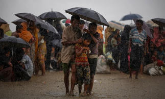 Rohingya refugees shelter from torrential rain after crossing the border into Bangladesh.