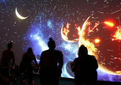 In this Jan. 3, 2017 photo, a view of the solar system silhouettes participants in a spinning class at Brooklyn's IMAXShift in New York. Cyclists on stationary bicycles watch musically-timed visuals on an IMAX screen in a tiered, theatre-like setting while a stunning array of visuals provide a sensory-overloading experience based on the instructor's choreography. (AP Photo/Kathy Willens)