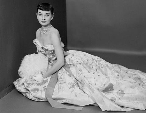 Slide 1 of 35: Audrey Hepburn seated and wearing a ball gown of Bianchini flowered silk taffeta, designed by Adrian.