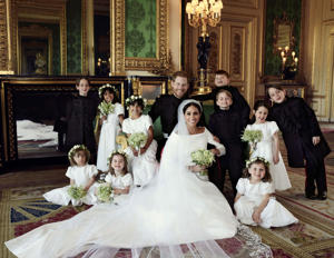 a group of people sitting at a wedding: Harry and Meghan's official wedding portrait sees the kids cheesing at the camera.