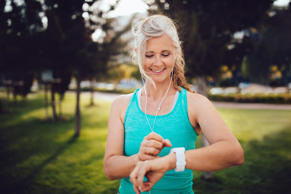 Fit senior woman listening to music and checking her pulse and jogging time on smartwatch