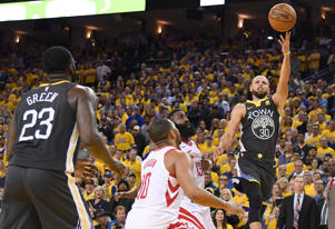 Warriors guard Stephen Curry (30) shoots against Houston Rockets guard Eric Gordon (10) and guard James Harden (13) during the fourth quarter in game four of the Western conference finals of the 2018 NBA Playoffs at Oracle Arena.