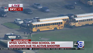 a car parked in a parking lot: In this image taken from video, law enforcement officers respond to a high school near Houston after an active shooter was reported on campus, in Santa Fe, Texas.