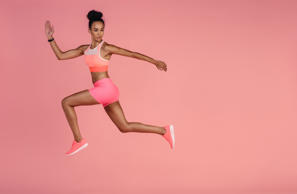 Woman in sportswear running over pink background. Full length shot of healthy young african woman sprinting.