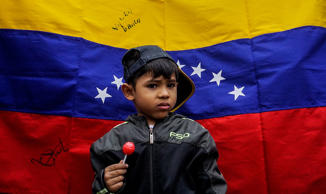 A boy stands in front of a Venezuelan national flag during a protest by Venezuelans living in Colombia against President Nicolas Maduro and the presidential election being held in their country, at the Monument to the Heroes in Bogota, on May 20, 2018. (Photo by Luis ACOSTA / AFP)        (Photo credit should read LUIS ACOSTA/AFP/Getty Images)