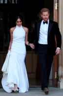 The newly married Britain's Prince Harry, Duke of Sussex, (R) and Meghan Markle, Duchess of Sussex, (L) leave Windsor Castle in Windsor on May 19, 2018 after their wedding to attend an evening reception at Frogmore House. (Photo by Steve Parsons / POOL / AFP)        (Photo credit should read STEVE PARSONS/AFP/Getty Images)