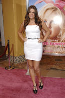 "22-year-old Khloé shows up to the ""pink"" carpet premiere of House Bunny in a fitted white mini and black peep-toe heels. She keeps her chestnut-colored hair in loose waves and completes the look with a thin, black belt around her waist."