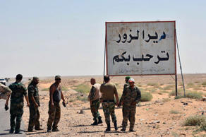 "This file photo released Sept. 3, 2017, by the Syrian official news agency SANA, shows Syrian troops and pro-government gunmen standing next to a sign in Arabic which reads, ""Deir el-Zour welcomes you,"" in the eastern city of Deir el-Zour, Syria."