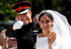 Britain's Prince Harry gestures next to his wife Meghan as they ride a horse-drawn carriage after their wedding ceremony at St George's Chapel in Windsor Castle in Windsor, Britain, May 19, 2018. REUTERS/Damir Sagolj TPX IMAGES OF THE DAY