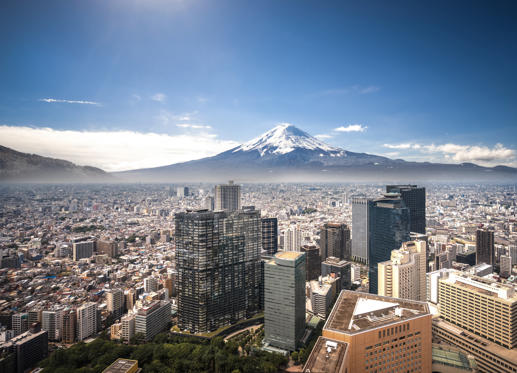 Slide 1 of 21: View of Mt. Fuji and office buildings in Shinjuku, Tokyo.