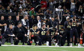 a group of people standing in front of a crowd posing for the camera: NFL's national anthem policy is a mandate, not a compromise