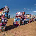 a group of people on a beach with Cadillac Ranch in the background: 4 Weird Roadside Attractions You Need to See On Your Next Vacation