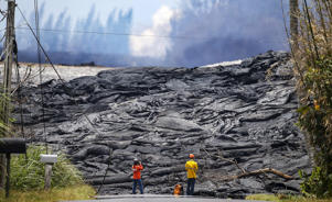 PAHOA, HI - MAY 24: USGS workers observe lava from a Kilauea volcano fissure in Leilani Estates, on Hawaii's Big Island, on May 24, 2018 in Pahoa, Hawaii. An estimated 40-60 cubic feet of lava per second is gushing from volcanic fissures in Leilani Estates.