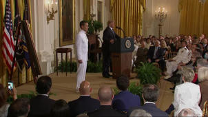a group of people in a room: Trump awards Medal of Honor to SEAL team leader