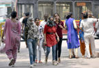 Pedestrians cover their face to protect themselves from scorching heat